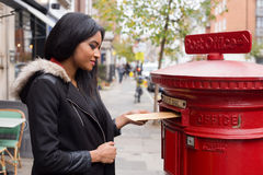Posting letters. A young woman posting letters Stock Photos