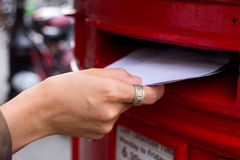 Posting letters. A young woman posting her letters Stock Images