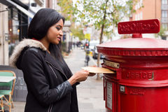 Posting letters. A young woman posting a letter Royalty Free Stock Photography