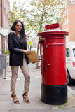 Posting mail. A young woman posting letters Royalty Free Stock Image