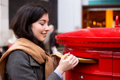 Posting mail. A young woman posting letters Royalty Free Stock Photos