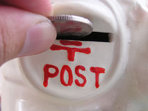 Posting money. Closeup of hand inserting coin (ten pence) into a coin box with postal-box theme stock photo