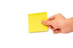 Posting a sticky note. A hand sticking a yellow sticky note Stock Images