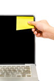 Posting a sticky note. A hand posting a yellow sticky note Stock Images