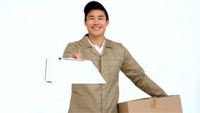 Postino asiatico sorridente che passa documento al segno video d archivio