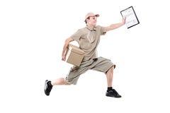 Postino su una fretta che trasporta pacchetto Immagini Stock