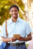 Postino Walking Along Street che consegna le lettere Immagini Stock