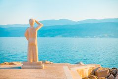 POSTIRA, CROATIA - JULY 12, 2017: Famous stone monument of person looking into a horizon in a small town Postira - Croatia, island. POSTIRA, CROATIA - JULY 12 Stock Photos