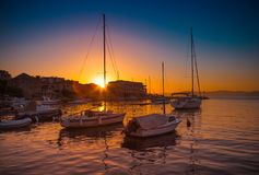 POSTIRA, CROATIA - JULY 12, 2017: Lots of fancy yachts at the sunset in the harbor of a small town Postira - Croatia, island Brac. POSTIRA, CROATIA - JULY 12 Royalty Free Stock Photo
