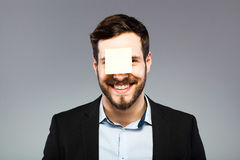 Postit on man face. Businessman with postit on the face Stock Photos