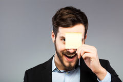 Postit on man face. Smiling man with postit on the face Royalty Free Stock Photos
