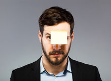 Postit on man face. Young man with blank note on the face, postit Stock Photos