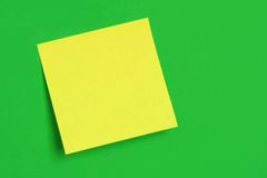 Postit Note on Green. A yellow postit note, with neon green background stock photos