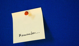 Postit with remember note. Yellow postit with remember note on blue background Royalty Free Stock Photography
