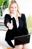 Postive businesswoman with thumb up using a laptop Stock Photography