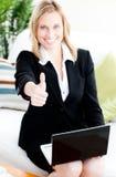 Postive Geschäftsfrau mit dem Daumen oben unter Verwendung eines Laptops Stockfotografie