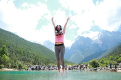 Postive happy life, Asian Chinese jump by a lake. Asian Chinese woman yoga by a lake, Yulong snow capped mountains on the background, beautiful landscape Royalty Free Stock Photography