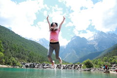 Postive happy life, Asian Chinese jump by a lake. Asian Chinese woman yoga by a lake, Yulong snow capped mountains on the background, beautiful landscape Stock Photo