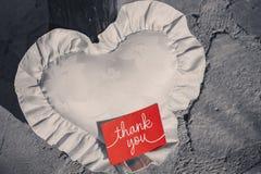 Postkarte mit der Aufschrift danken Ihnen auf einem roten Hintergrund auf einem weißen Kissen in Form eines Herzens Lizenzfreies Stockfoto