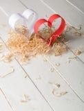 Postkarte zum Valentinstag Weißes und rotes Herz gemacht von den Papierstreifen Dekorative gelockte Sägespäne Stockbild