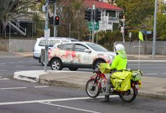 Postman from Australia Post delivers mail on a motorbike in Brisbane Australia with Queensland houses in background circa June 201. A postman from Australia Post Royalty Free Stock Images