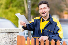 Postman delivering letters to mailbox of recipient Stock Images