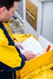 Postman delivering letters to mailbox of recipient royalty free stock image