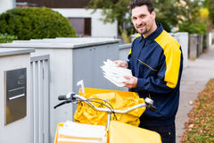 Postman delivering letters to mailbox of recipient. Nn stock photography