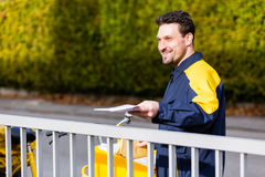 Postman delivering packet wrapped as present Royalty Free Stock Images