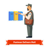 Postman delivers letter to a colorful  mailbox Stock Photos