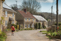 Postman delivers letters in English village. SHIPTON GORGE, UK - APRIL 12, 2016:  Mailman delivers letters in pretty English village Royalty Free Stock Photography