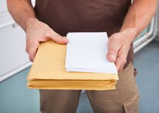 Postman holding letters. Close-up Photo Of Mature Postman Holding Letters stock photos