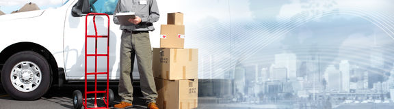 Postman with parcel box. Postman with parcel boxes near delivery truck royalty free stock image