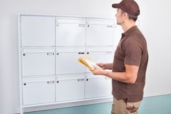 Postman putting letters in mailbox Royalty Free Stock Photography