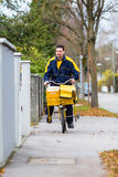 Postman riding his cargo bike carrying out mail Stock Photography