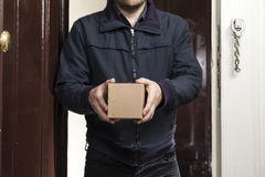 Postman with small package. Postman delivers a small package royalty free stock images
