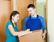 Postman in uniform delivered parcel to girl. At home royalty free stock photos