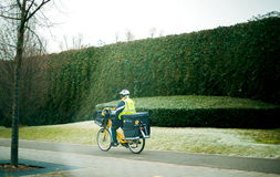 Postman worker on bicycle on cold day Royalty Free Stock Photos