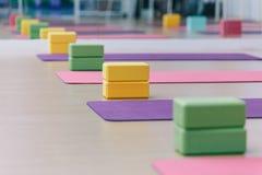 Posto Colourful dei blocchetti e delle stuoie di yoga sul pavimento di legno di struttura Ready per il codice categoria di yoga fotografia stock libera da diritti