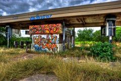Posto de gasolina abandonado coberto de vegetação coberto com os grafittis Imagens de Stock Royalty Free