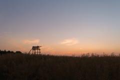 Posto di guardia di legno situato in un campo durante il tramonto Fotografie Stock