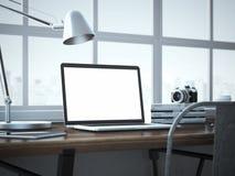 Posto di lavoro alla moda con il computer portatile moderno nell'interno del sottotetto Immagine Stock