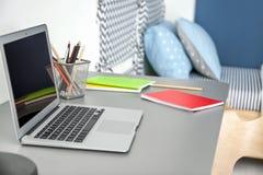 Posto di lavoro comodo con il computer portatile sullo scrittorio fotografie stock
