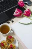 Posto di lavoro con i tulipani ed il computer portatile Fotografia Stock