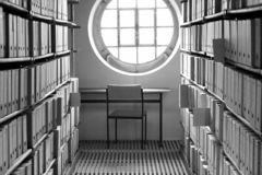 Posto di lavoro con la tavola e sedia sotto una finestra soleggiata circondata dagli scaffali di libro e dai chilometri delle sca immagini stock libere da diritti