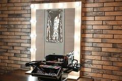 Posto di lavoro del truccatore professionista con lo specchio ed il cosmetico Fotografie Stock