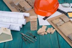 Posto di lavoro dell'architetto - disegni di costruzione e strumenti di ingegneria, poca casa, casa di modello dai blocchi di leg fotografia stock