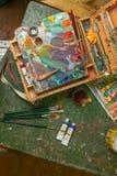 Posto di lavoro dell'artista con le spazzole e le pitture ad olio Fotografia Stock