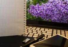 Posto di lavoro dell'ufficio con il taccuino, lo Smart Phone, la penna, l'azionamento istantaneo e il wordpad con i fiori viola immagini stock libere da diritti