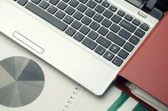 Posto di lavoro moderno di affari con il computer portatile ed alcune carte con il grafico Fotografia Stock Libera da Diritti
